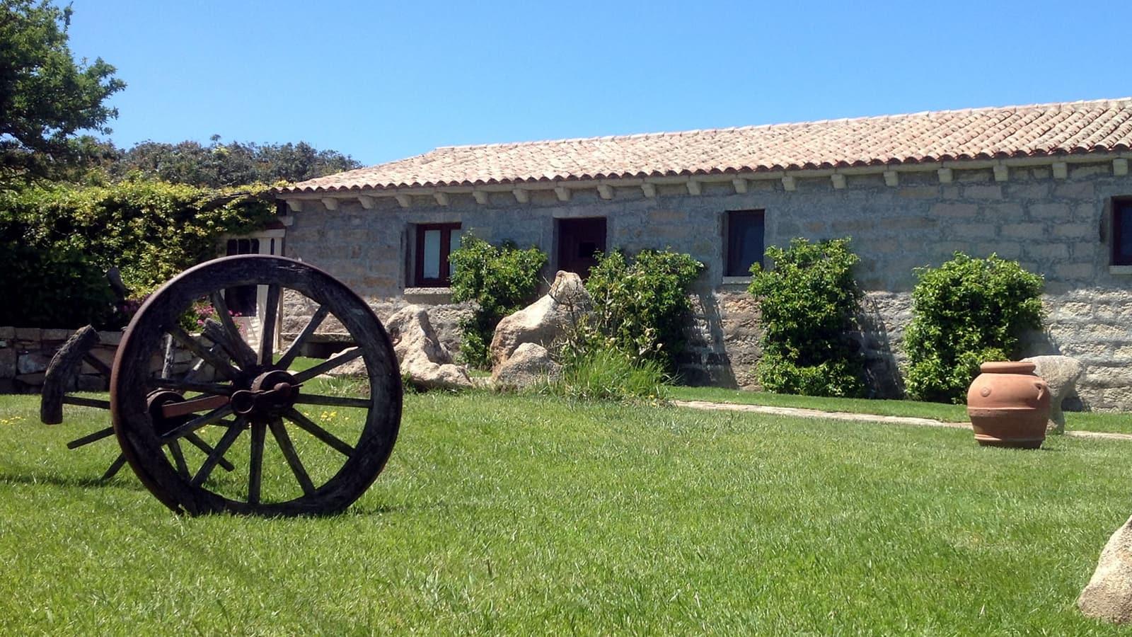 un prato verde e l'edificio dell'agriturismo La Kustera