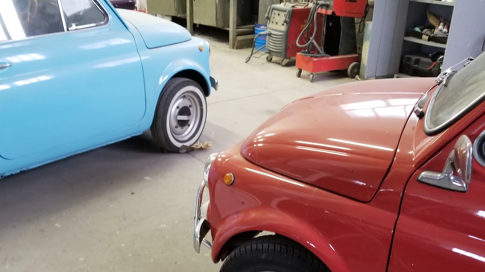 due Fiat 500, una celeste ed una rossa, in carrozzeria