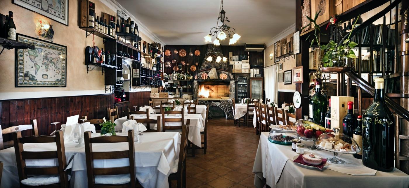 interno del ristorante La Pitraia, con tavoli ed un camino acceso