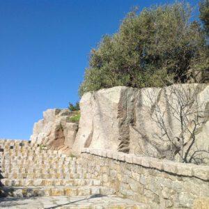 una scalinata in granito con un masso e degli olivastri vicini