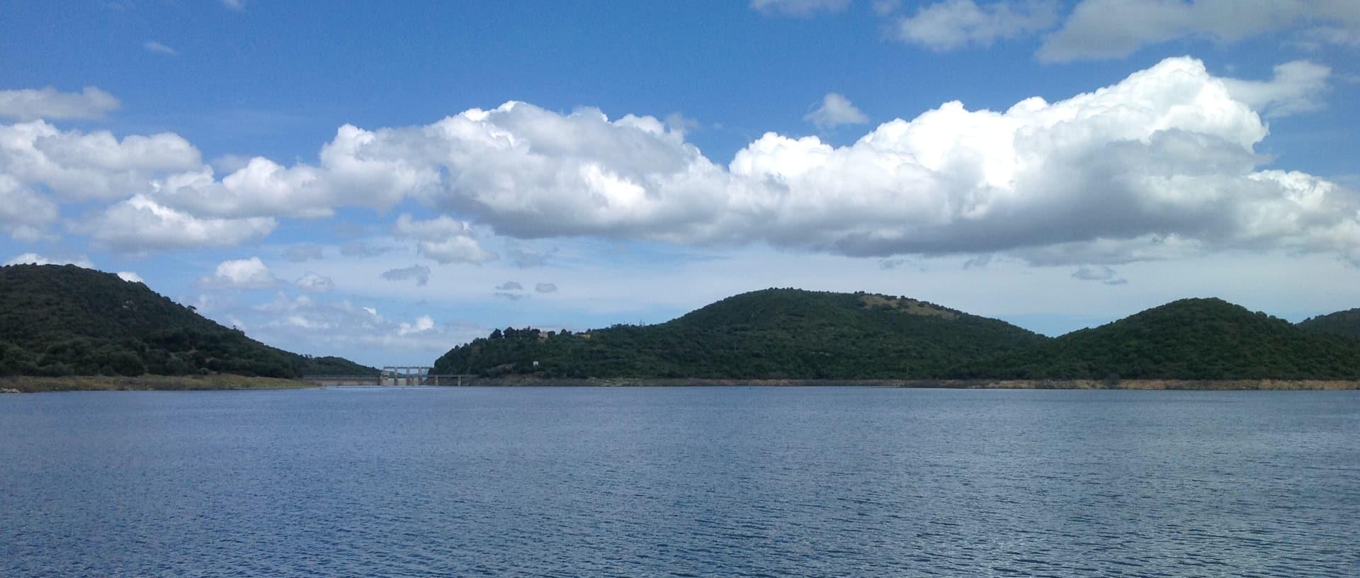 il lago del liscia visto da un'imbarcazione, con la diga sullo sfondo.